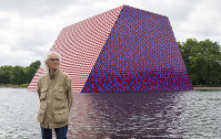 Artist Christo attends the unveiling of his first UK outdoor exhibit, The London Mastaba, on the Serpentine Lake in Hyde Park, central London, on June 18, 2018. (Dominic Lipinski/PA via AP)