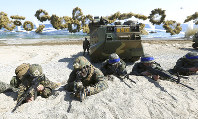 """In this March 12, 2016, file photo, Marines of the U.S., left, and South Korea wearing blue headbands on their helmets, take positions after landing on a beach during the joint military combined amphibious exercise, called Ssangyong, part of the Key Resolve and Foal Eagle military exercises, in Pohang, South Korea. U.S. President Donald Trump promised to end """"war games"""" with South Korea, calling them provocative, after meeting North Korean leader Kim Jong Un on June 12, 2018. His announcement appeared to catch both South Korea and the Pentagon by surprise. (Kim Jun-bum/Yonhap via AP, File)"""