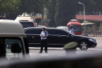 The motorcade which is believed to be carrying North Korea leader Kim Jong Un passes by policemen as it leaves the Beijing Capital International Airport in Beijing, on June 19, 2018. (AP Photo/Andy Wong)