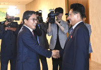 In this photo provided by the South Korea Culture And Sports Ministry, North Korean head delegate Won Kil U, right, shakes hands with his South Korean counterpart Jeon Choong-ryul as he arrives to hold a meeting at the southern side of Panmunjom in the Demilitarized Zone, Monday, June 18, 2018. (South Korea Culture And Sports Ministry via AP)