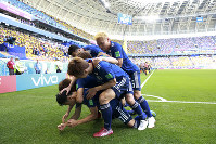 Teammates crowd over Japan's Shinji Kagawa after he scored from the penalty spot his side's first goal against Colombia during a group H match at the 2018 soccer World Cup in the Mordavia Arena in Saransk, Russia, on Tuesday, June 19, 2018. (AP Photo/Eugene Hoshiko)