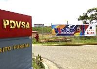 マドゥロ大統領を支持する横断幕が掲げられた国営石油会社PDVSAの石油関連施設の入り口=ベネズエラ東部エルフリアルで2018年5月23日、山本太一撮影