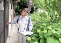 空き家の玄関が施錠されているか確認する黒沢友一さん=埼玉県秩父市で