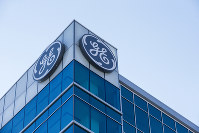 In this Jan. 16, 2018, file photo, the General Electric logo is displayed at the top of their Global Operations Center in the Banks development of downtown Cincinnati. (AP Photo/John Minchillo)