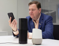 In this June 14, 2018 photo, Gareth Gaston, Executive Vice President and Head of Omnichannel Banking at US Bank, discusses voice assistant banking with a mobile phone, an Amazon Echo, center, and a Google Home, right, in New York. (AP Photo/Mark Lennihan)