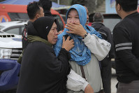 Relatives weep at Tigaras port after learning that their family members are among the passengers of a ferry which sank on Monday, in Simalungun, North Sumatera, Indonesia, on June 19, 2018. (AP Photo/ Lazuardy Fahmi)