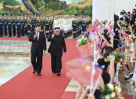 In this photo provided by China's Xinhua News Agency, Chinese President Xi Jinping, left, North Korean leader Kim Jong Un, right, walk together during a welcoming ceremony for Kim at the Great Hall of the People in Beijing, on June 19, 2018. (Shen Hong/Xinhua via AP)