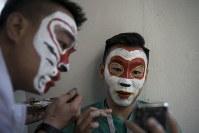【ポルトガル・モロッコ】スマートフォン画面で顔のペイントを確認する中国から来たサポーター=AP
