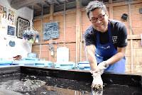 藍染めを体験する外国人観光客=徳島県藍住町徳命の「藍の館」で、松山文音撮影