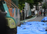 The street where a 9-year-old girl was killed by a collapsing concrete block wall surrounding her school's pool is seen in Takatsuki, Osaka Prefecture, on June 21, 2018. The school reopened that morning. (Mainichi)