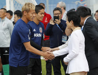 Japan's Princess Hisako, right, and Keisuke Honda, left, shake hands prior to a training session of the Japanese national team at the 2018 soccer World Cup in Kazan, Russia, on June 21, 2018. (AP Photo/Eugene Hoshiko)