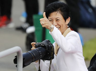 Japan's Princess Hisako gives a thumbs-up as she takes photographs during a training session of the Japanese national team at the 2018 soccer World Cup in Kazan, Russia, on June 21, 2018. (AP Photo/Eugene Hoshiko)