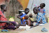 やせ細るザンデ・エリアちゃん(5)=中央。手にしたカップも大きく見えるほど、腕はやせ細っている=南スーダン・ジュバで2018年4月24日、小川昌宏撮影