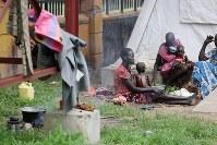 やせ細ったザンデ・エリアちゃん(5)=左から2人目=の母マリ・ケジさん(左端)ら家族は、テント脇で自炊し、少ない食べ物を分け合っていた=南スーダン・ジュバで2018年4月24日、小川昌宏撮影