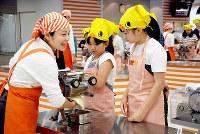 インスタントラーメンをつくる工程を体験する子どもたち。頭にかぶっているのは「ひよこちゃんバンダナ」=大阪府池田市のカップヌードルミュージアム大阪池田で、中尾卓司撮影