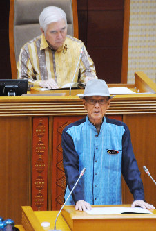 In this June 12, 2018 file photo, Okinawa Gov. Takeshi Onaga wears a hat as he explains a bill he is submitting to the Okinawa Prefectural Assembly, in Naha. (Manichi)