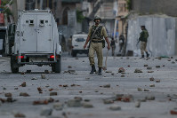 Indian paramilitary soldiers walk on a road dotted with bricks and stones thrown at them during a protest in Srinagar, Indian controlled Kashmir, on June 21, 2018. (AP Photo/Dar Yasin)