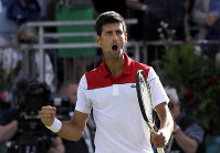 Novak Djokovic of Serbia celebrates winning his match against Grigor Dimitrov of Bulgaria during their singles tennis match at the Queen's Club tennis tournament in London, on June 21, 2018. (AP Photo/Kirsty Wigglesworth)