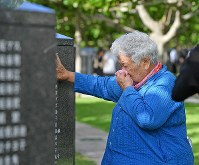 A bereaved woman cries when she touches the Cornerstone of Peace monument, on which the names of those who died in the Battle of Okinawa are engraved, at the Peace Memorial Park in Itoman, Okinawa Prefecture, on June 23, 2018. (Mainichi)