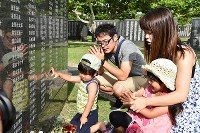 Bereaved family members offer prayers in front of the Cornerstone of Peace monument, on which the names of those who died in the Battle of Okinawa are engraved, at the Peace Memorial Park in Itoman, Okinawa Prefecture, on June 23, 2018. (Mainichi)