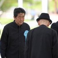 Prime Minister Shinzo Abe exchanges greetings with Okinawa Gov. Takeshi Onaga ahead of a ceremony in Itoman, Okinawa Prefecture, on June 23, 2018. (Mainichi)