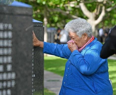 戦没者の名前が刻まれた「平和の礎」に触れて、涙を流す遺族の女性=沖縄県糸満市摩文仁の平和祈念公園で2018年6月23日午前8時18分、野田武撮影