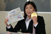 金メダルと、自らの活躍を報じる毎日小学生新聞を手に、小学生へのメッセージを語る村岡桃佳選手=米田堅持撮影