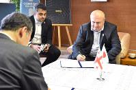 ラグビーワールドカップの事前キャンプに関する協定書に署名するジョージアラグビー協会のゴチャ・スヴァニゼ会長(右奥)と飯泉嘉門徳島県知事(手前)=徳島県庁で、松山文音撮影