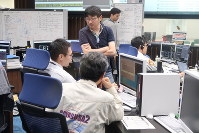 Hayabusa 2 project members examine telemetric data coming from the spacecraft at the mission control center in Sagamihara, Kanagawa Prefecture, on June 24, 2018. (Mainichi)