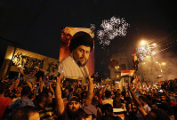 In this Monday, May 14, 2018 file photo, supporters of Shiite cleric Muqtada al-Sadr carry his image as they celebrate in Tahrir Square, Baghdad, Iraq. (AP Photo/Hadi Mizban, File)