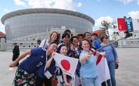 セネガル戦を前にロシアの人と記念写真を撮る日本のサポーター。奥は試合会場のエカテリンブルク・アリーナ=ロシア・エカテリンブルクで2018年6月24日、長谷川直亮撮影
