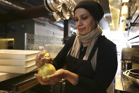 In this June 20, 2018 photo, Muna Anaee prepares a ball of khobz orouk, a flatbread she would eat frequently in her native Iraq, at the Tawla restaurant kitchen in San Francisco during the inaugural Refugee Food Festival. (AP Photo/Lorin Eleni Gill)
