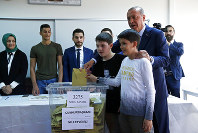 Turkey's President and ruling Justice and Development Party, or AKP, leader Recep Tayyip Erdogan casts his ballot in Turkey's elections at a polling station in Istanbul, Sunday, June 24, 2018. Turkish voters are voting Sunday in a historic double election for the presidency and parliament. (AP Photo/Lefteris Pitarakis)