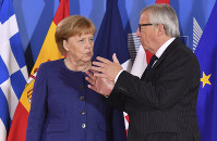 European Commission President Jean-Claude Juncker, right, speaks with German Chancellor Angela Merkel during an informal EU summit on migration at EU headquarters in Brussels, on June 24, 2018. (AP Photo/Geert Vanden Wijngaert, Pool)