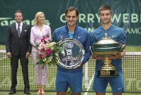 Croatia's Borna Coric, right, and Switzerland's Roger Federer, left, pose with the trophies during the winners ceremony at the Gerry Weber Open ATP tennis tournament in Halle, Germany, on June 24, 2018. Borna Coric beats Roger Federer in the match. (Friso Gentsch/dpa via AP)