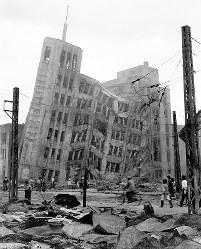 激しい揺れで大和百貨店(正面)も南側に傾いた。大名町交差点から南東を望む。左隣に見えるのは現在も当時の外観を残す福井信託(現三井住友信託銀行福井支店)。鉄筋コンクリート造り7階建ての大和百貨店は1945年7月の福井空襲でも焼け残り、福井市のシンボルとされた建物だった=福井市佐佳枝上町(現福井市中央1)で1948年6月撮影(写真説明協力・福井県立歴史博物館)