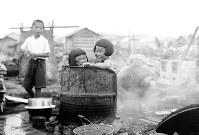 被災後にバラック建て住宅が建ち始めた福井駅南側の福井市日ノ出元町(現福井市中央1付近)で、ドラム缶風呂に入る子どもたち=1948年7月3日撮影(写真説明協力・福井県立歴史博物館)