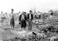 被災地で、亡くなった家族の冥福を祈る被災者=福井市で1948年6月撮影