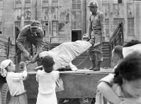 重傷者を移送するためトラックに乗せる連合国軍総司令部の兵士=福井市で1948年6月撮影