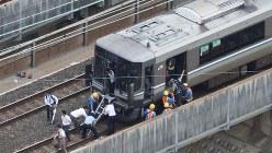 止まったままの列車を降りて、線路を歩く乗客たち=大阪府高槻市で、2018年6月18日午前9時53分、本社ヘリから三村政司撮影