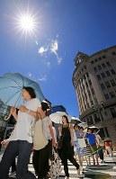 梅雨明けで青空が広がる銀座の街、日傘を差して歩く人たち=東京都中央区で2018年6月29日午後1時2分、梅村直承撮影