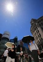 梅雨明けで青空が広がる銀座の街を、日傘を差して歩く人たち=東京都中央区で2018年6月29日午後0時43分、梅村直承撮影