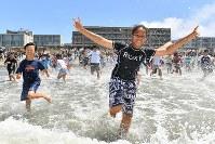 海開きで一斉に海へ駆け出す子どもたち=神奈川県逗子市の逗子海水浴場で2018年6月29日午前10時40分、渡部直樹撮影