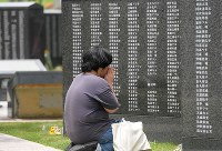 沖縄慰霊の日、戦没者の名前が刻まれた「平和の礎」の前で、手を合わせて冥福を祈る女性=沖縄県糸満市摩文仁の平和記念公園で23日、津村豊和撮影