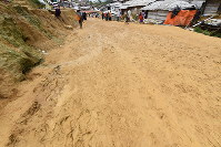A road at a refugee camp on the outskirts of Cox's Bazar in southeastern Bangladesh is muddy after rainfall on June 24, 2018. Pedestrians slipped and fell. (Mainichi)