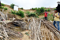 A shelter crushed by a landslide at a refugee camp on the outskirts of Cox's Bazar in southeastern Bangladesh is pictured on June 24, 2018. Three Rohingya refugees who were living in the shelter were killed. (Mainichi)