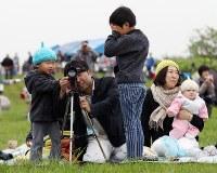 落下して炎上する小型ロケット「MOMO(モモ)」2号機を望遠鏡で見つめる家族連れ=北海道大樹町で2018年6月30日午前5時43分、貝塚太一撮影