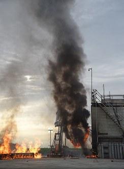 打ち上げ後に落下して爆発し燃え続ける小型ロケット「MOMO(モモ)」2号機(左下)と発射台周辺=北海道大樹町で2018年6月30日、貝塚太一撮影(リモートカメラ使用)