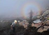 ブロッケン現象が現れる中、登山道の岩場を登る登山者=山梨県富士吉田市の富士山吉田口8合目で2018年6月30日午後4時31分、手塚耕一郎撮影