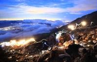 7月1日の山開きを前に、富士山に登る人たち(60秒露光)=富士山吉田口八合目付近で2018年6月30日午後7時51分、玉城達郎撮影